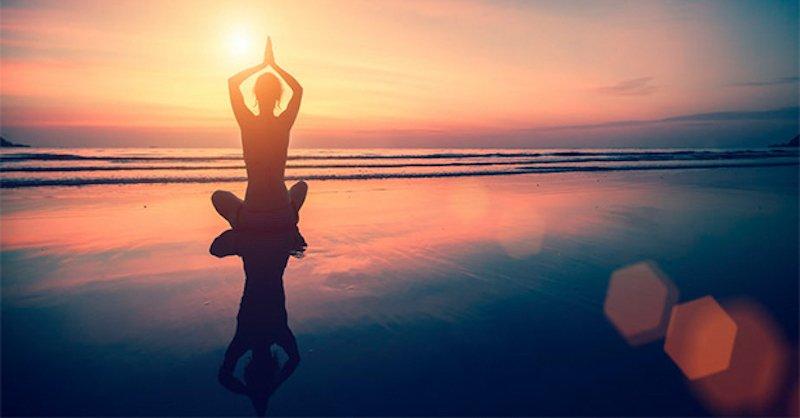 A woman sitting on the beach meditating
